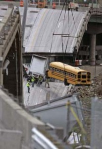 Workers remove a school bus from the interstate 35W bridge collapse site in Minneapolis, Minn., Sunday, Aug. 12, 2007. The school bus was carrying 52 children from a visit to a water park when it dropped with the bridge during the collapse. All the children survived the fall. (AP Photo/Nati Harnik)